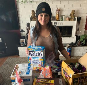 Erin Weyman stands behind a pile of snacks to be donated