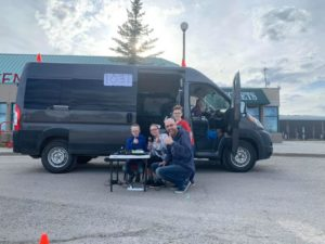 Man and his children in front of their family van