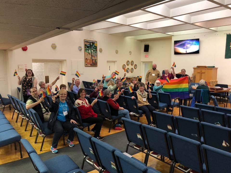 a church group waving rainbow flags